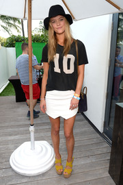 Nina Agdal contrasted her loose top with a sexy white mini skirt.