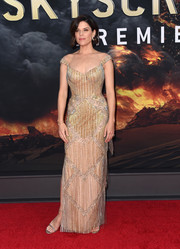 Neve Campbell complemented her gorgeous dress with gold ankle-strap heels.