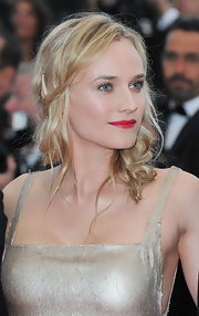 Diane Kruger put a unique spin on her wavy tresses with twisted tendrils pinned in a side swept hairstyle. Ripe red lipstick completed her glamorous look.