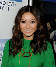Brenda Song glamed up her kelly green dress with a bronze circular statement necklace.