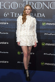 Sophie Turner matched her top with a pair of white ruffle shorts.