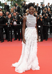 Lupita Nyong'o looked ethereal in a high-neck white Dior Couture gown with an embroidered bodice and a petal-appliqued skirt at the Cannes Film Festival screening of 'Sorry Angel.'