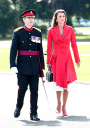 Queen Rania looked perfectly polished in a textured red coat by Givenchy at the Sovereign's Parade.