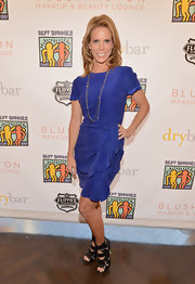 Cheryl Hines opted for a classic cocktail dress with this purple dress with draping.