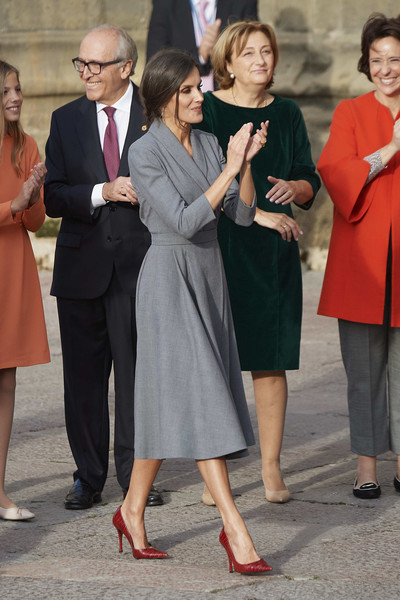 Queen Letizia gave her dress a pop of color with a pair of red croc-embossed pumps by Magrit.