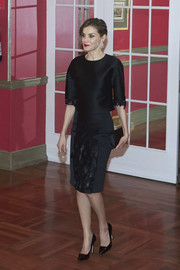 Queen Letizia of Spain accessorized with a simple black satin clutch by Felipe Varela.