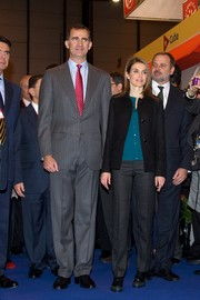 Princess Letizia stayed low-key in a black jacket, teal blouse, and gray slacks during the FITUR Tourism Fair.