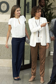 Queen Letizia of Spain kept it simple and relaxed in a loose white blouse and navy slacks while visiting the 016 Telefonic Hotline Central.