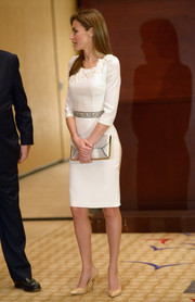 Princess Letizia complemented her lovely dress with a chic snakeskin envelope clutch.