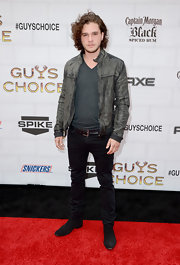 Kit wore a worn-in gray leather jacket with his charcoal V-neck.