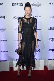 Bianca Balti paired her alluring frock with an embellished black purse.