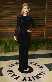 Taylor Swift epitomized classic sophistication in a long-sleeve, beaded black gown by Julien Macdonald during the Vanity Fair Oscar party.