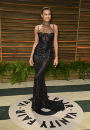 Irina Shayk looked va-va-voom in an embellished black corset gown by Versace during the Vanity Fair Oscar party.