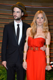 Sienna Miller got all blinged up with layers of gold-tone cuffs by Alexander McQueen for the Vanity Fair Oscar party.