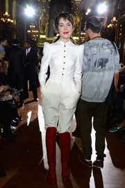 Ulyana Sergeenko rocked a pair of red knee-high boots with her white jumpsuit.