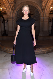 Pamela Anderson went conservative in a short-sleeve black midi dress at the Stella McCartney fashion show.