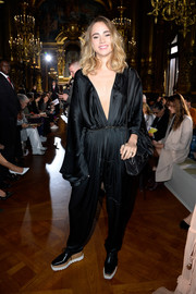 Suki Waterhouse looked exotic at the Stella McCartney fashion show in a draped black jumpsuit with a deep-V plunge.