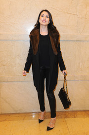 Yasmine Tordjman looked super stylish in a black wool coat with a brown fur collar during the Stephane Rolland fashion show.