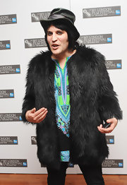 Noel wears a black faux fur coat over a printed tunic.
