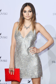 Daya paired her dress with a beaded red clutch.