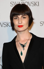 Erin O'Connor, at the Swarovski Fashionation in Milan, accessorized her outfit by wearing a simple chain with a crystal-bordered long teardrop green gemstone pendant.
