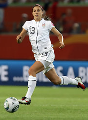 Alex Morgan sprints across the pitch in Nike soccer cleats.