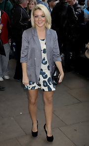 Sheridan wears a gray business style blazer over a print dress.