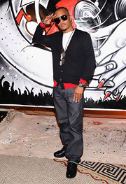 T.I. rocked dark denim jeans with a black and red cardigan.