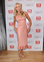 Aviva Drescher posed wearing a peach satin dress at the Andy Cohen book signing party.
