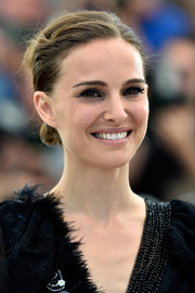 Natalie Portman attended the photocall for 'A Tale of Love and Darkness' wearing a youthful side-parted chignon.