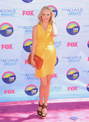 Candice Accola sported a striking blend of colors with this orange leather clutch and yellow wrap dress combo at the 2012 Teen Choice Awards.