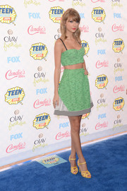 Taylor Swift wore bright yellow Charlotte Olympia strappy sandals with her green separates for a fun mix of colors.