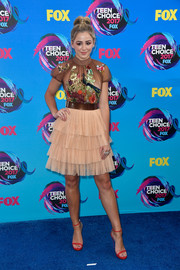 Chloe Lukasiak went ultra girly at the 2017 Teen Choice Awards in a LeiLou by Alex Dojčinović cocktail dress with a sheer, embellished bodice and a tiered skirt.