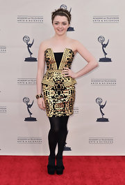 Maisie Williams sported a cool gold and black strapless dress with peplum detailing for her red carpet look.