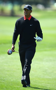 Tiger Woods embraced the traditional, preppy golf style when he sported this black crewneck over a red polo.