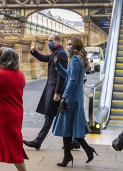 Kate Middleton teamed a black Strathberry leather clutch with a blue coat and tall suede boots for day 2 of her tour across the country.