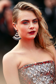 Cara Delevingne added more sparkle to her sequined dress with a pair of fan-shaped dangling earrings.