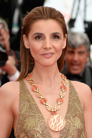 Clotilde Courau finished off her look with an eye-catching coral and gold statement necklace.