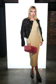 Suki Waterhouse accessorized with a pink crocodile fold-over clutch for a splash of feminine color.