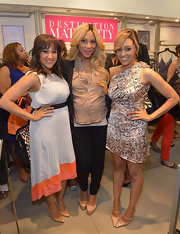 Tia Mowry chose a flowing gray dress with a pink and orange hem for her look at the launch of Milky! in Beverly Hills.
