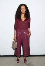 Solange Knowles looked uncharacteristically low-key in a burgundy cashmere V-neck sweater by Tibi while attending the label's fashion show.