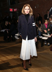 Olivia Palermo attended the Tibi show in a sleek navy coat with white sleeve stripes.