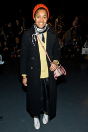 Tamu McPherson bundled up in a long black wool coat and a sweater for the Tibi fashion show.