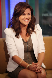 90's star Tiffani Thiessen looked flirty and feminine at the FOX studios wearing an olive dress and white blazer. She paired the look with loose curls and face framing layers.