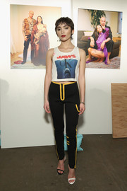 A pair of black neoprene pants with yellow trim completed Rowan Blanchard's outfit.