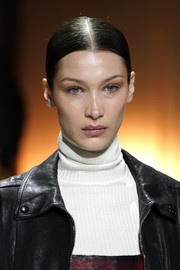 Bella Hadid wore her hair in a center-parted updo at the Tod's Fall 2020 show.
