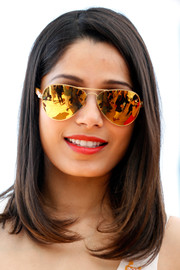Freida Pinto accessorized with a pair of mirrored gold aviators.