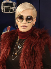 Rita Ora amped up the funky vibe with round sunnies by Miu Miu teamed with a red fur vest.