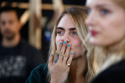 Cara Delevingne was spotted backstage at the Topshop Unique show rocking pastel-blue nail polish.