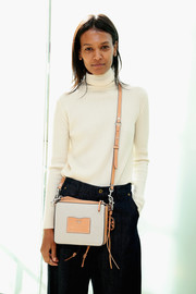 Liya Kebede accessorized with a two-tone leather cross-body bag by Tory Burch.